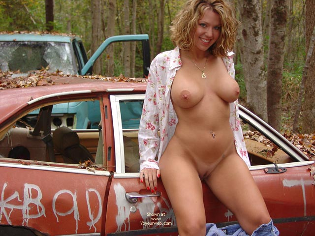 Pic #1 - Devilish Grin - In The Woods , Devilish Grin, Stripping Outside, Standing By Automobiles, In The Woods, Nude In Car Junk Yard, Shaved Blonde