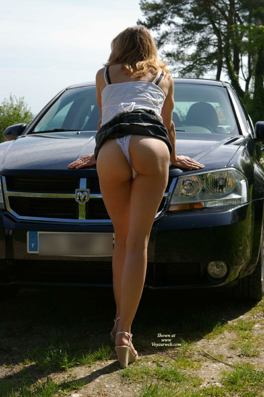 Pic #1 - Great Ass In Short Skirt And White Lace Panties - Blonde Hair, Heels, Long Hair, Long Legs , White Lace Panties, White Spaghetti Strap Top, Skirt Hiked Up, Rear View, Bent Over The Hood Of A Ram, Public Upskirt, White G-string