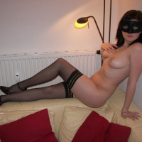 Sitting On Top Of Couch Naked In Mask And Stockings - Brunette Hair, Heels, Long Legs, Stockings